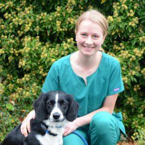 Grace Lane Vet team member Hannah Bayes headshot with black and white spaniel