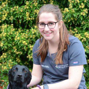 Grace Lane Vet team member Kimberley Johnson headshot with a little black labrador