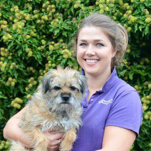 Grace Lane Vet team member Sophie Hopkins headshot holding border terrier